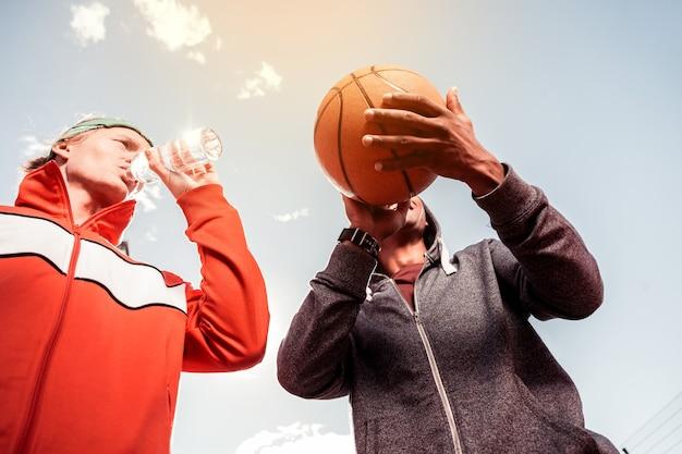 진짜 스포츠. 좋은 유쾌한 남자의 손에있는 농구 공의 낮은 각도