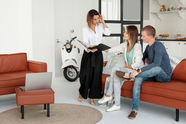 Агент по недвижимости разговаривает с мужчиной и женщиной