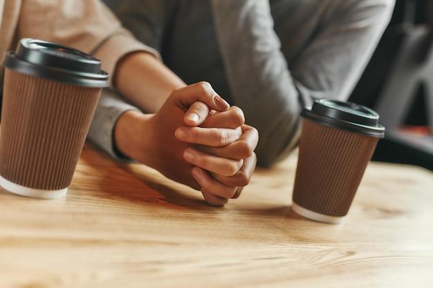 本当のサポートの友達がモダンなカフェでミーティングをする