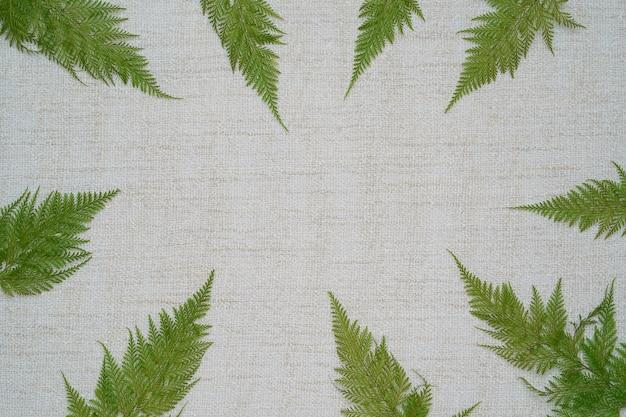 갈색 원사 배경에 실제 열대 고사리 잎