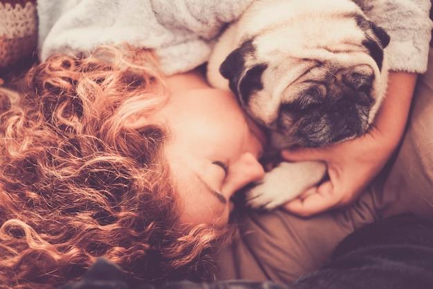 眠っている中年の美しい女性白人の間の本当の本当の愛と保護、彼女の親友の犬のパグ。人生の概念における家庭での友情と関係
