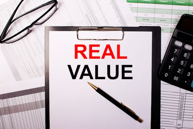 Real value is written on a white sheet of paper, near the glasses and the calculator.