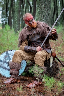 Real viking sharpening his sword with a stone