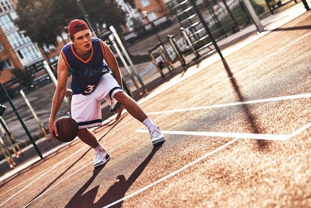 진짜 승자. 야외에서 시간을 보내는 동안 농구를하는 스포츠 의류에서 젊은 남자의 전체 길이
