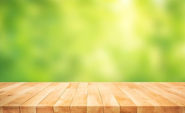 ぼやけた新鮮な緑の庭の背景に本物の木のテーブルトップテクスチャ。