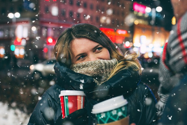 Real young couple walking together in night city under snow, kissing