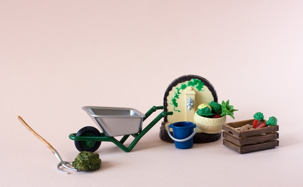 Realistic figures of farm or garden tools with box of vegetables