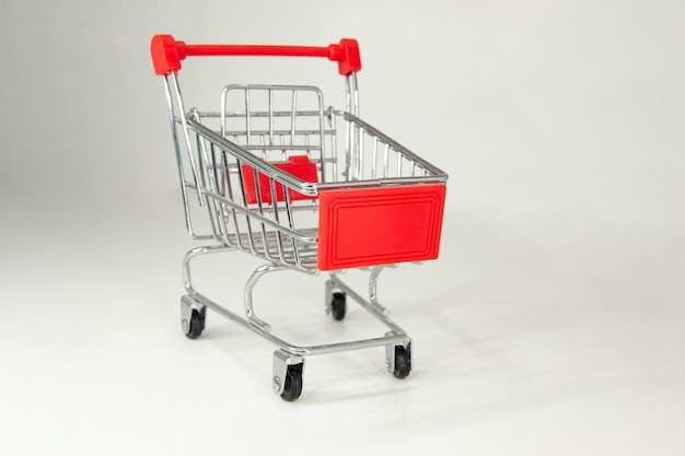 Realistic iron mini shopping cart with red plastic parts. white background. horizontal photography.
