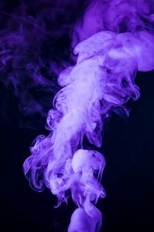 黒の背景に現実的な紫色の煙