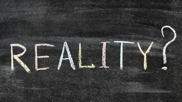 Reality with question mark handwritten on the school blackboard