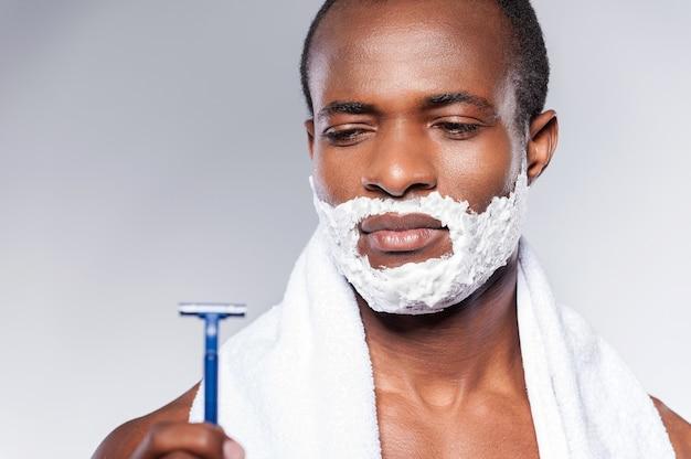 Действительно плохая бритва. молодой африканский мужчина без рубашки смотрит на бритву и выражает негатив, стоя на сером фоне