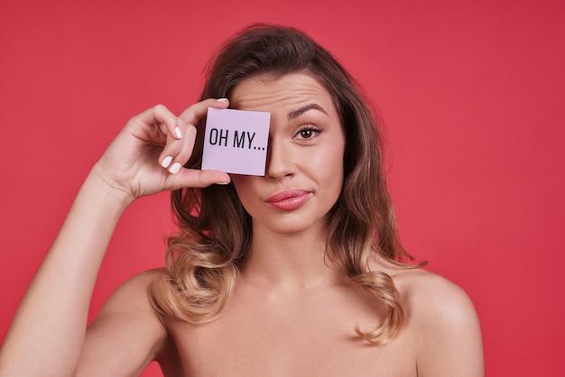 Действительно? скучающая молодая женщина, закрывающая глаз небольшим плакатом и смотрящая в камеру, стоя на розовом фоне