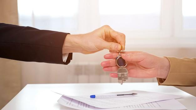Риэлтор передает ключи даме после подписания договора аренды.
