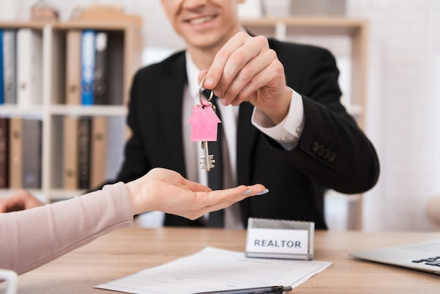 Realtor gives woman keys with pink keychain.