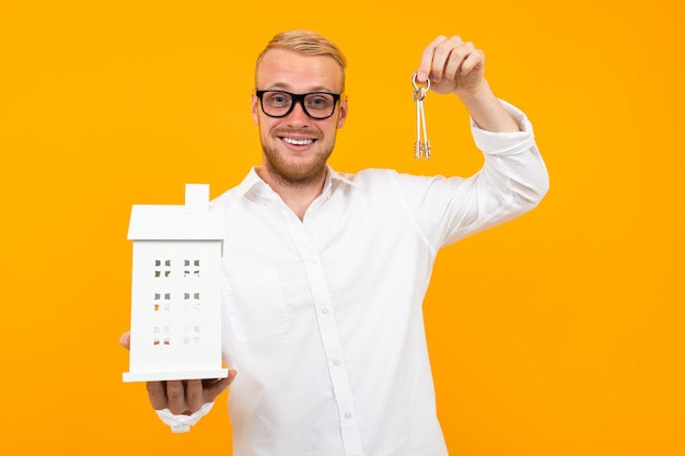 Realtor guy holds a house model in his hand on a yellow with copy space