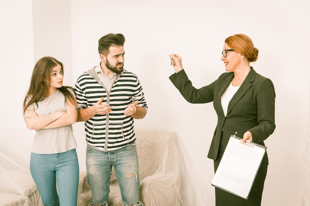 Realtor proposing to sign a cotract to man and woman who are not agree
