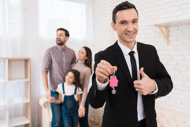 Realtor in suit holds keys with key fob in form of house.