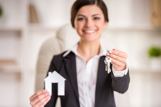 Realtor woman is showing home for sale sign and keys.