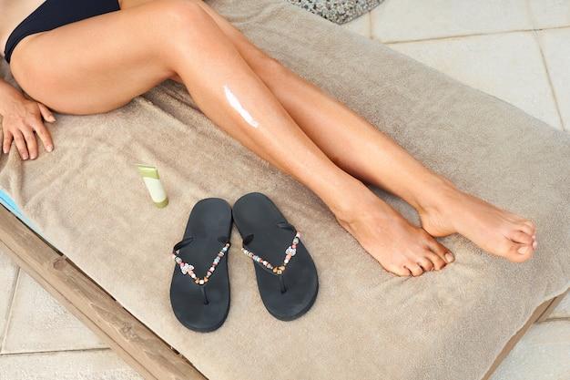 Leg¡脚にリーマ。女性の手が肌に保湿ローションを適用しています。美容とボディケア。セルライトからの保護。サンスキンプロテクション。日焼けローション。