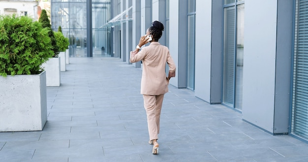 Rear of african american beautiful woman in medical mask talking on mobile phone and walking outside at business center. happy businesswoman speaking on cellphone and strolling. back view.