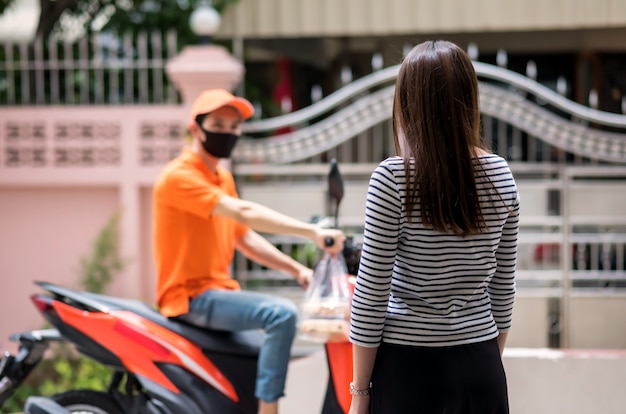 Rear asian woman wait food while courier delivery man with face mask arrive to house by riding motorbike.