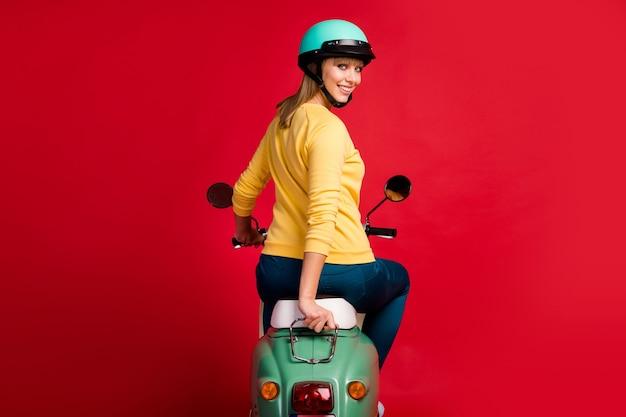 赤い壁に原付ルックカメラを運転している陽気な女の子の後ろの後ろの後ろ