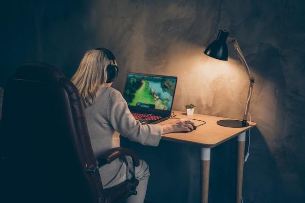 Сзади, сзади, сзади, вид на нее, она симпатичная, сосредоточенная, сосредоточенная, концентрированная седая светловолосая бабушка, сидящая в кресле, играющая в командную игру vr, победа в промышленном лофте, интерьер в современном бетонном стиле