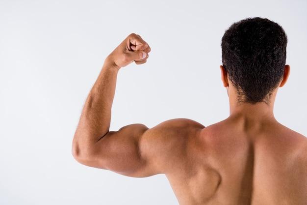 筋肉を示すスポーティーな日焼けした男の身体培養ステロイドタンパク質の後ろの後ろのビュー
