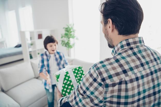 明るい白のモダンなインテリアハウスのリビングルームの屋内でプレティーンの息子のイベントにギフト購入ボックスを与える2人の素敵な陽気な陽気な嬉しい人のお父さんパパの後ろ姿の肖像画