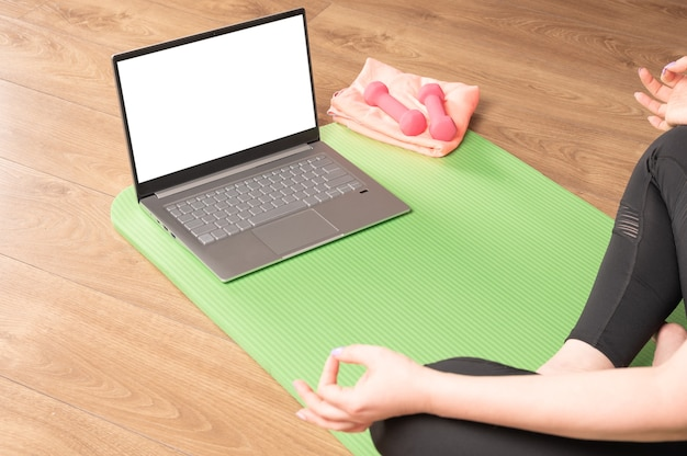 Rear back over shoulder view at fit sporty healthy calm woman sit on mat in lotus pose watching online yoga class meditate do breathing exercises