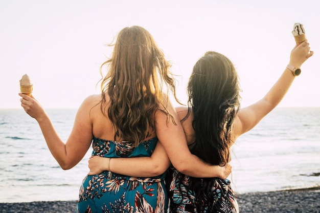 Rear back view of couple of women friends hug and enjoy together the summer eating an ice cream