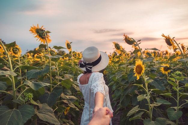 Rear of beauty woman in white dress holding hands a couple in sunflower field at evening