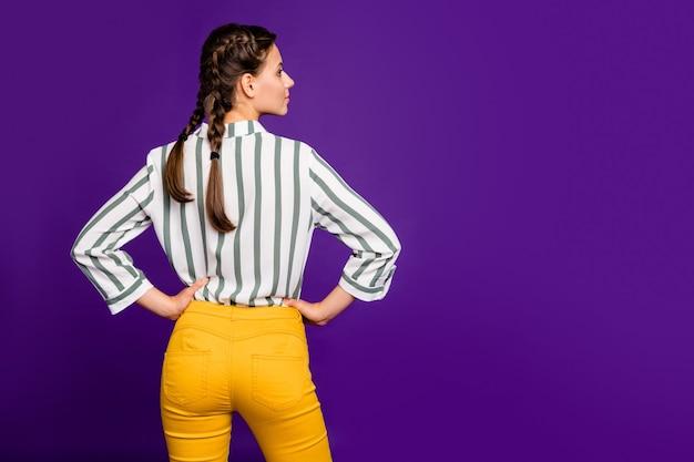 横に手を持って真剣に空のスペースを着用ストライプシャツ黄色のズボン孤立した紫色の背景を保持している美しいかわいいビジネス女性のプロフィールビュー写真の後ろの後ろ