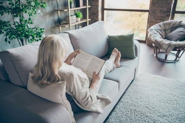 Вид сзади сзади фотография пожилой блондинки, лежащей на удобном диване, диване, чтение любимого исторического романа, хорошая одежда для свободного времени в бежевой пастельной одежде, плоская гостиная в помещении