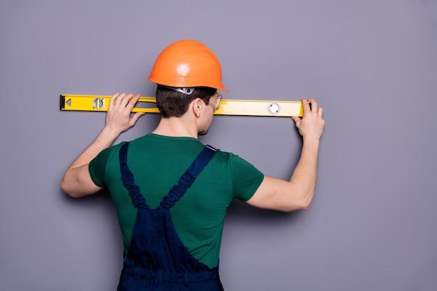 Сзади сзади фотография красивого мужского рабочего парня, опытного инженера, измеряющего длину стойки, футболку, защитный комбинезон, защитный шлем, очки, изолированные серую стену