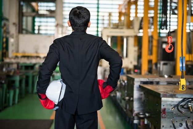 黒のスーツ、赤いボクシンググローブ、白いヘルメットを身に着けた後部のビジネスマンは、covid19パンデミック病の産業闘争の準備ができています。執拗な闘争と成功の製造工場産業。