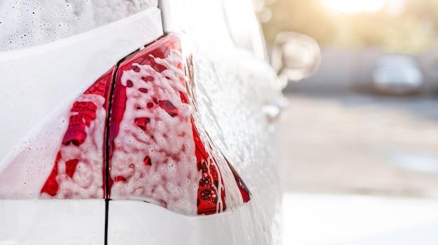 洗車中に泡で覆われた後部車のヘッドライトをクローズアップ