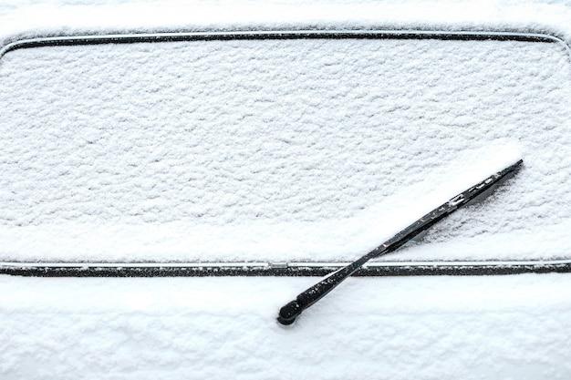 雪の中でワイパーが付いている後部車の窓