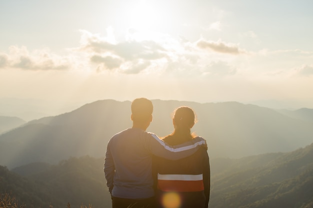 Rear of couple love stand on top mountain looking view with mist and cloud.