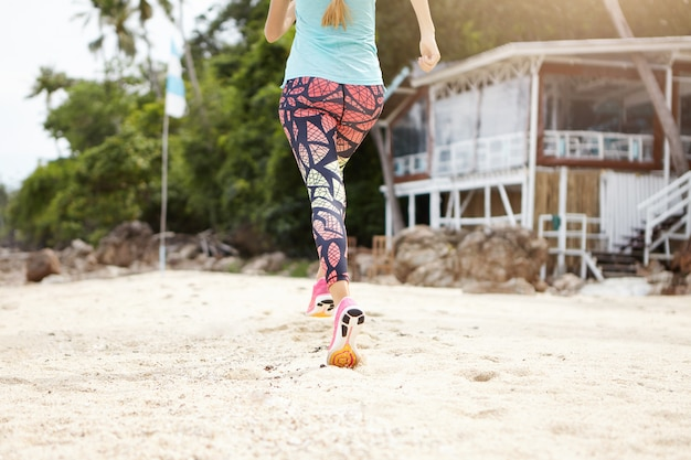 Rear cropped view of caucasian woman runner wearing colorful leggings and sneakers doing jogging exercises outdoors on beach.