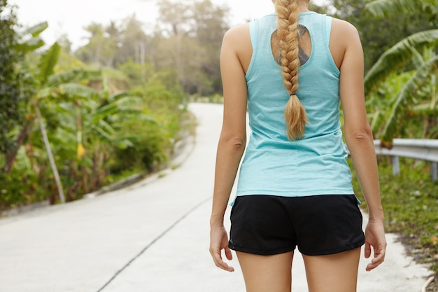 Rear cropped view of female jogger with long braid having rest after morning run in fresh air.