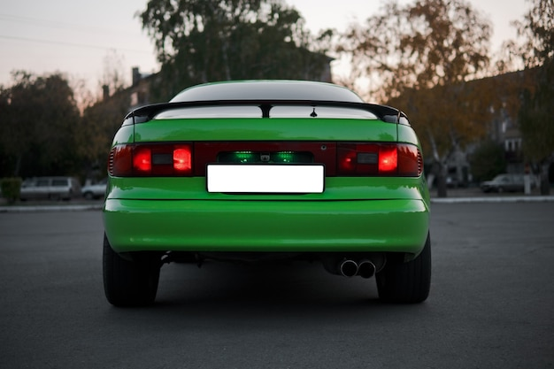 Задняя часть зеленого и черного спортивного автомобиля. японский олдтаймер.