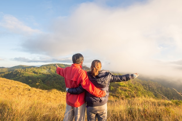 Rear of happy couple love stand on top mountain looking view with mist and cloud at doi langka luang, chiang rai province. soft focus.