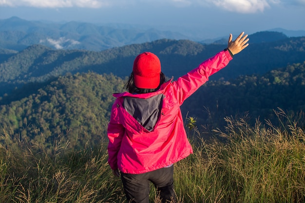 Rear of happy woman stand on top mountain looking view with mist and cloud at doi langka luang, chiang rai province. soft focus.