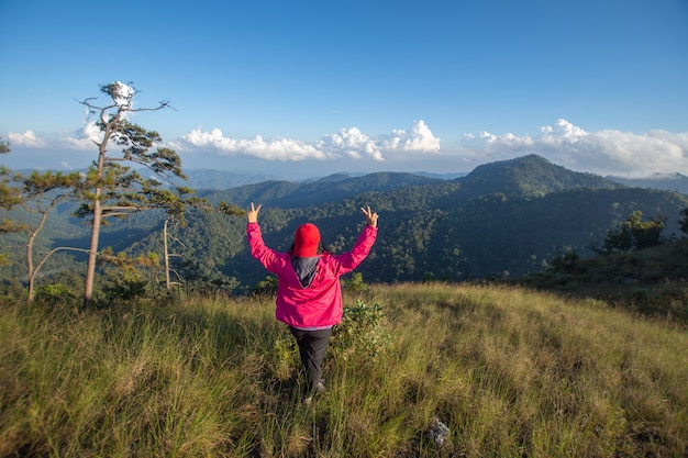 Rear of happy woman stand on top mountain looking view with mist and cloud.