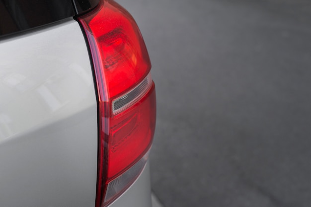 Rear light on new silver automobile on road