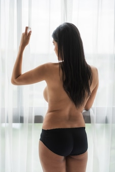 Rear of naked topless asian prostitute woman look at window with sad vibes or feeling.