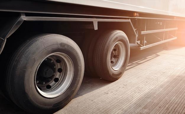 Задняя часть грузового автомобиля с большим прицепом на колесах