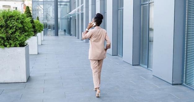 携帯電話で話し、ビジネスセンターで外を歩いている医療マスクのアフリカ系アメリカ人の美しい女性の後部。携帯電話で話したり散歩したりする幸せな実業家。背面図。