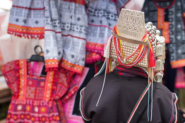 상점에서 손으로 만든 어린이 드레스와 의상을 판매하는 전통 드레스를 입은 akha 여성의 후면.